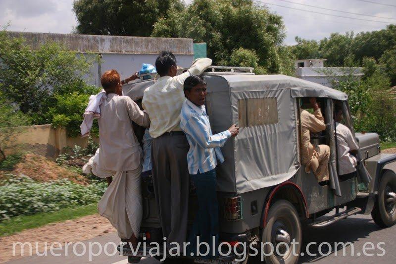 Gente encaramada a la parte trasera del Jeep, India