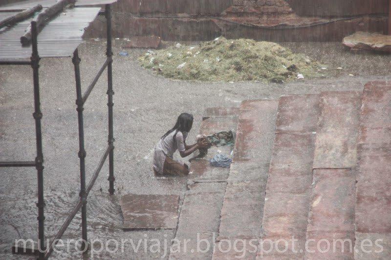 Chica aprovecha la lluvia para limpiar la ropa, Delhi