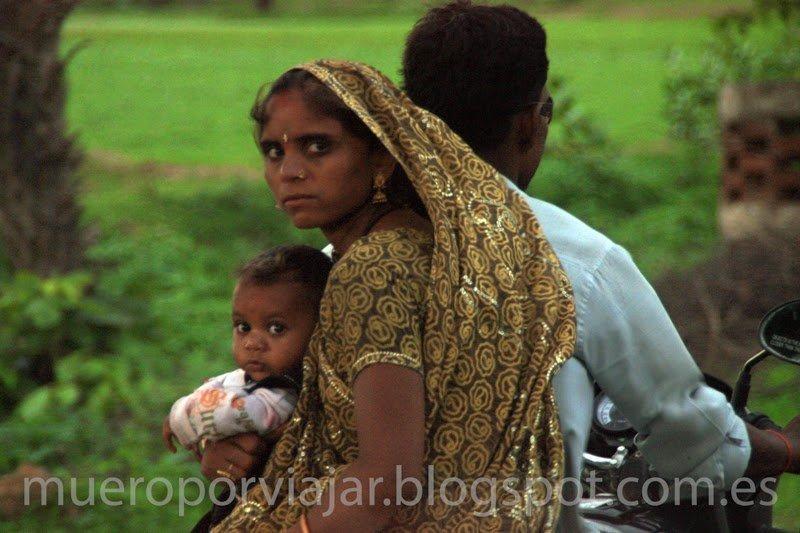 Mujer con su hijo viajando de paquete en una moto, India