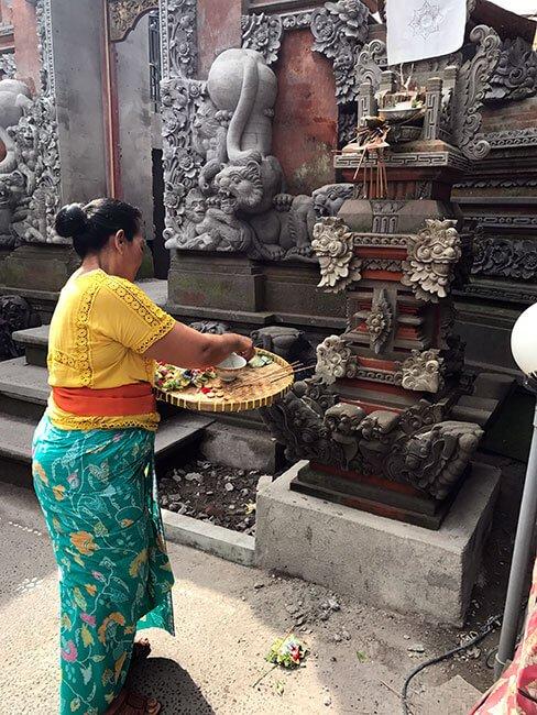 Una mujer poniendo ofrendas en el Palacio Real de Ubud